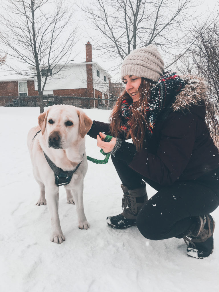 Claire kneeling down to her dog in the snow.